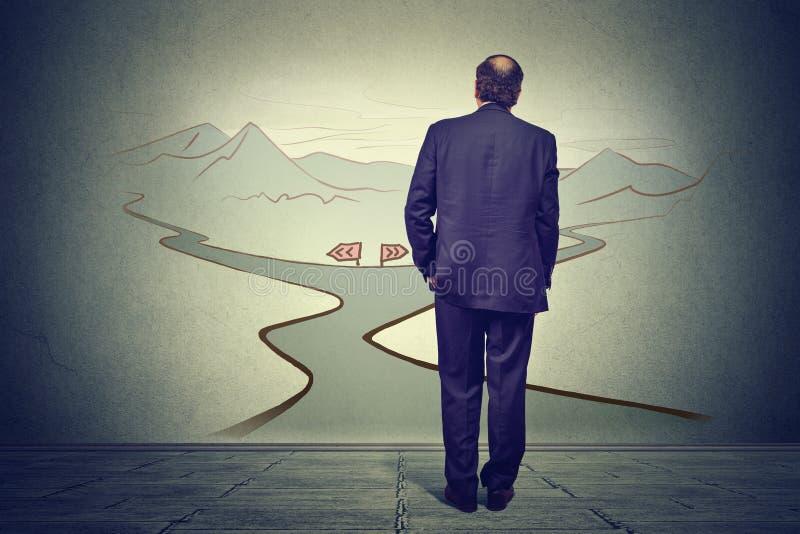 Biznesowy mężczyzna myśleć decydować przed dwa drogami obrazy stock