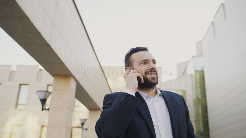 Biznesowy mężczyzna opowiada na telefonie komórkowym robi transakcjom i odprowadzeniu blisko nowożytnych budynków biurowych obrazy stock