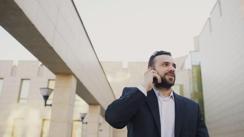Biznesowy mężczyzna opowiada na telefonie komórkowym robi transakcjom i odprowadzeniu blisko nowożytnych budynków biurowych zdjęcie royalty free