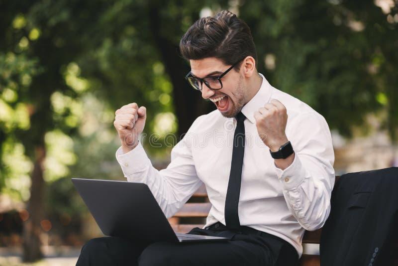 Biznesowy mężczyzna outdoors w parkowym używa laptopie robi zwycięzcy gestykulować zdjęcie stock