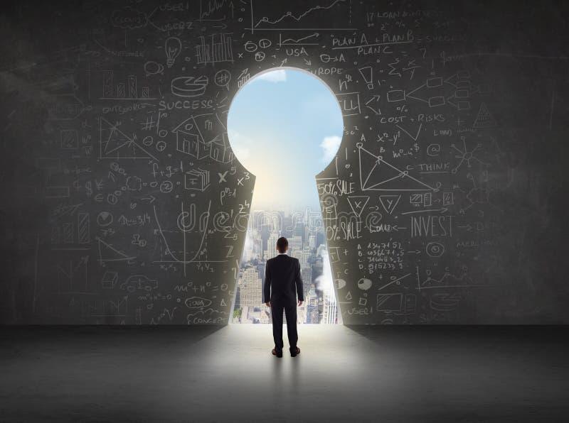 Biznesowy mężczyzna patrzeje keyhole z jaskrawym pejzażu miejskiego pojęciem zdjęcie stock