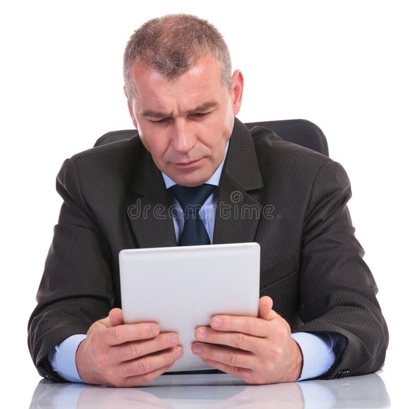 Biznesowy mężczyzna patrzeje koncentrujący przy jego pastylką obrazy royalty free
