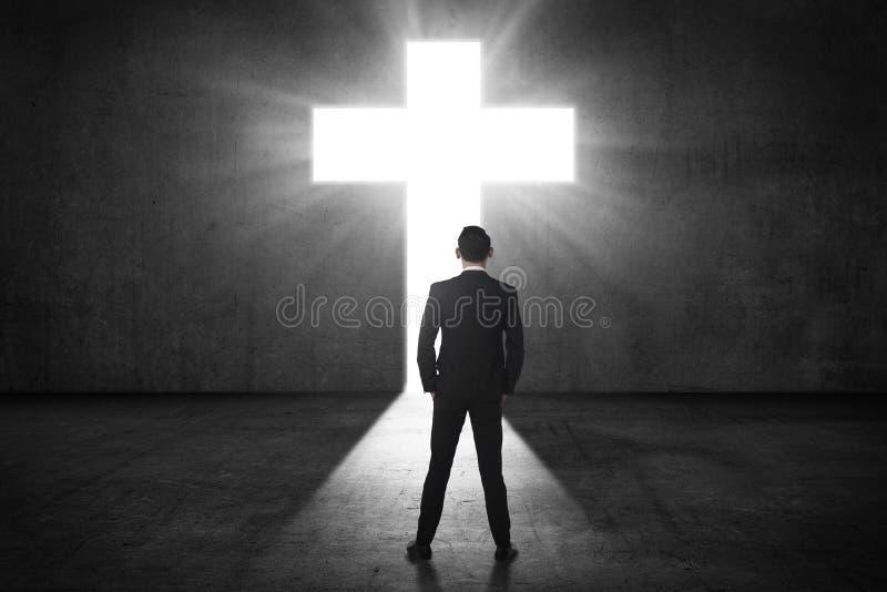 Biznesowy mężczyzna patrzeje olśniewającego krzyż na ścianie obraz royalty free