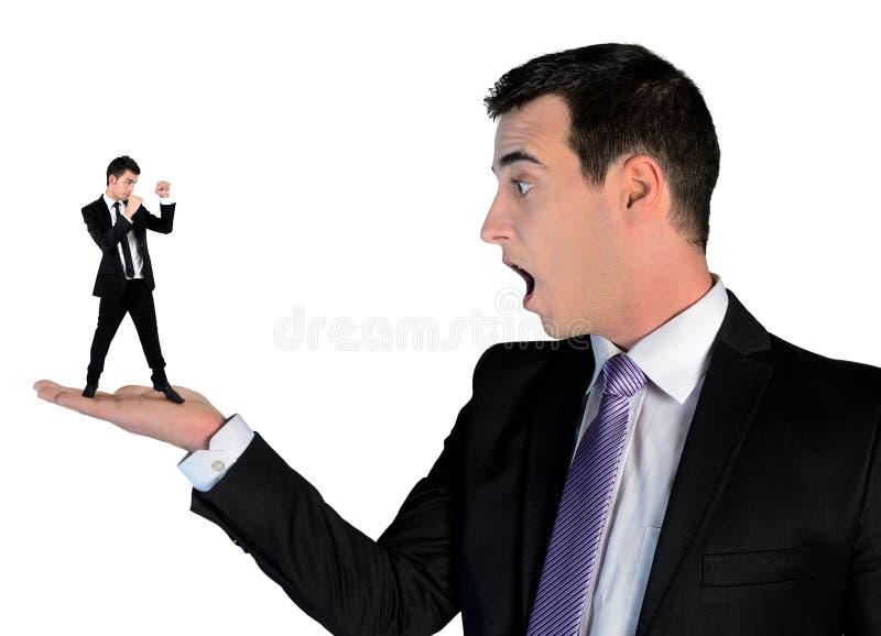 Biznesowy mężczyzna patrzeje szokujący na małym mężczyzna zdjęcie stock