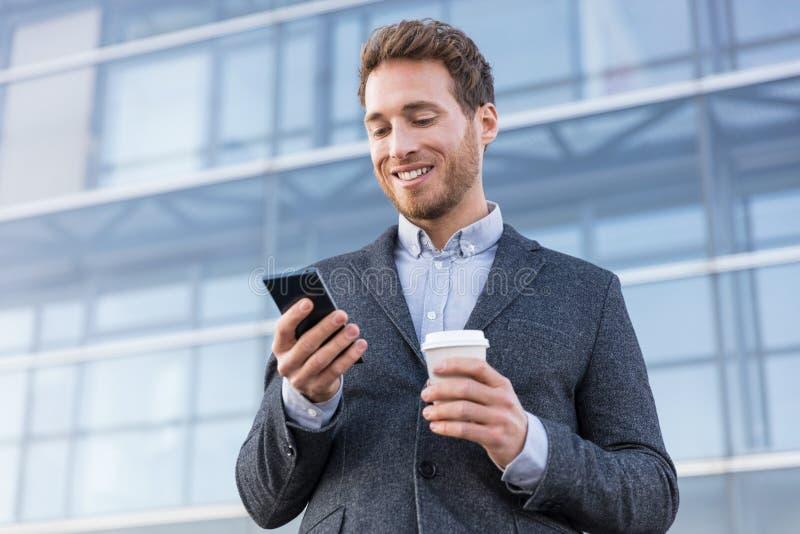 Biznesowy mężczyzna patrzeje telefon wiadomości texting tekst pije kawę na ranek przerwie przy pracy biurem Biznesmena styl ?ycia obraz stock