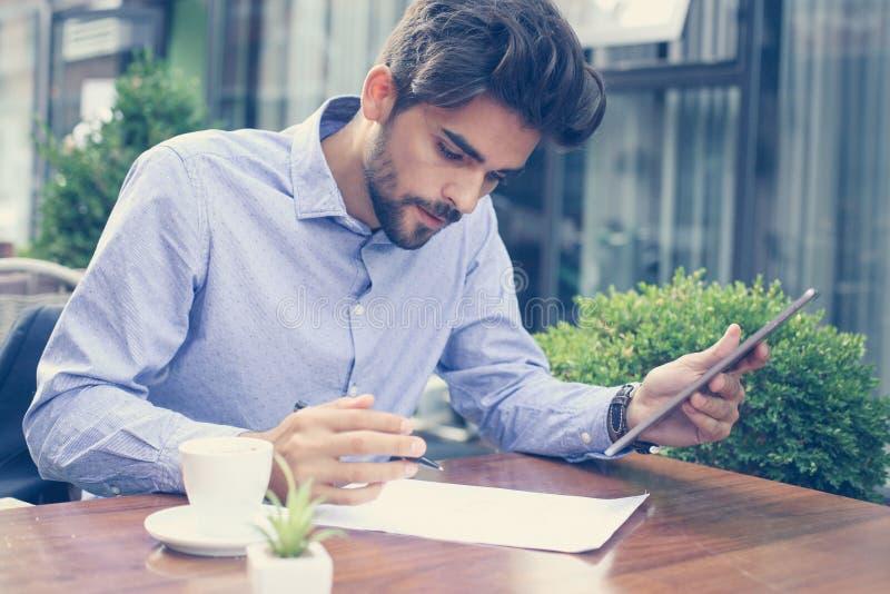 Biznesowy mężczyzna pracuje na cyfrowej pastylce w ulicznej kawiarni obraz royalty free