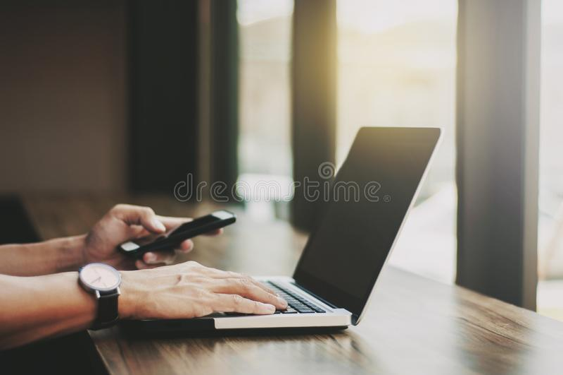 Biznesowy mężczyzna pracuje na laptopie i używa mobilnego mądrze telefon przy miejsce pracy fotografia royalty free