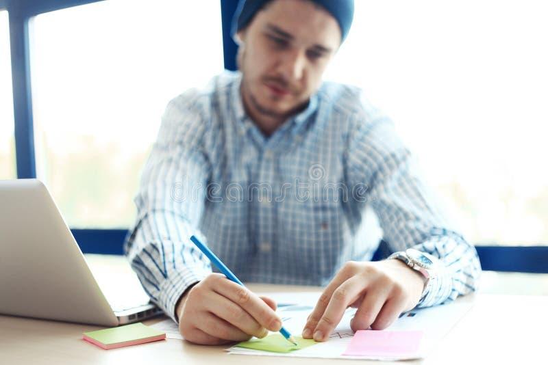 Biznesowy mężczyzna pracuje przy biurem z laptopem i dokumentami na jego biurku zdjęcie stock