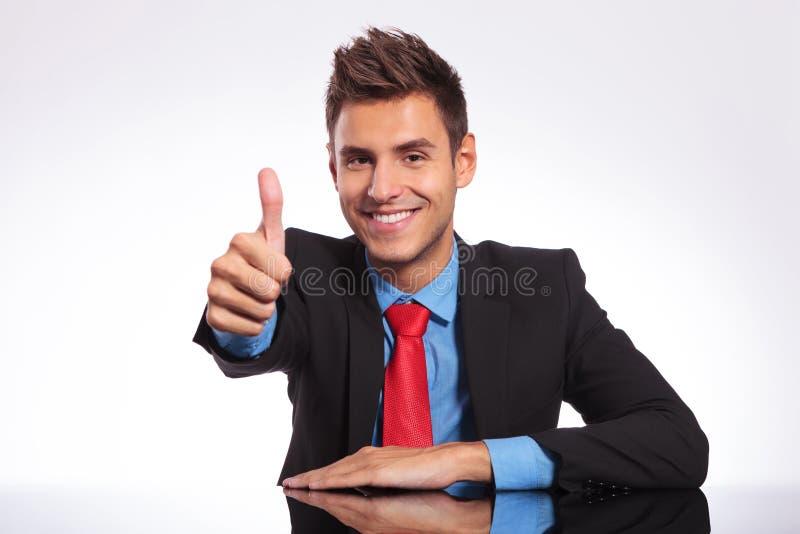 Biznesowy mężczyzna przy biurkiem pokazuje kciuk up zdjęcia royalty free