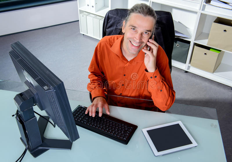 Biznesowy mężczyzna przy jego dzwonić i biurkiem zdjęcia stock