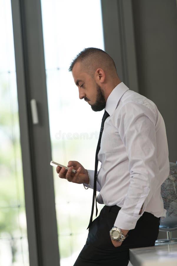 Download Biznesowy Mężczyzna Texting Na Telefonie Komórkowym W Nowożytnym Biurze Obraz Stock - Obraz złożonej z bankowość, szachrajka: 42525769