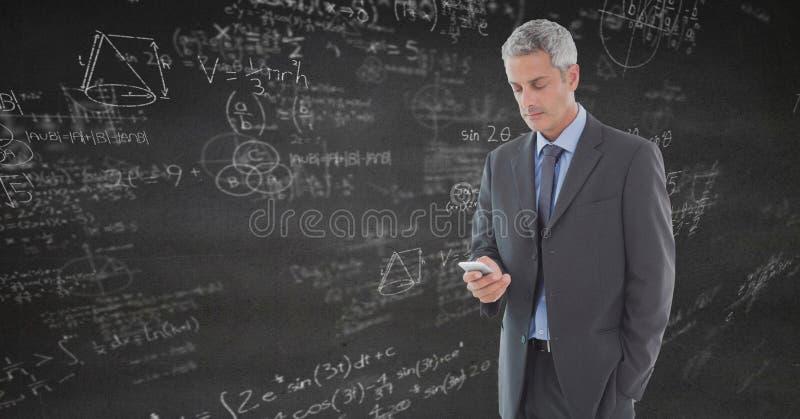Biznesowy mężczyzna texting przeciw popielatej ścianie z matematyką doodles fotografia royalty free