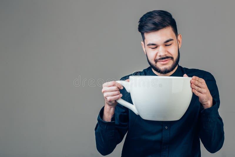 Biznesowy mężczyzna trzyma śmieszną ogromną i dużych rozmiarów filiżankę czarna kawa w kofeinie obrazy stock
