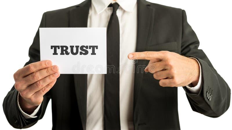 Biznesowy mężczyzna trzyma białego karcianego saying zaufanie fotografia stock