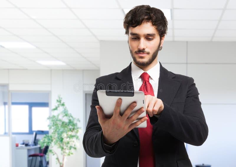 Biznesowy mężczyzna trzyma jego pastylkę obrazy stock