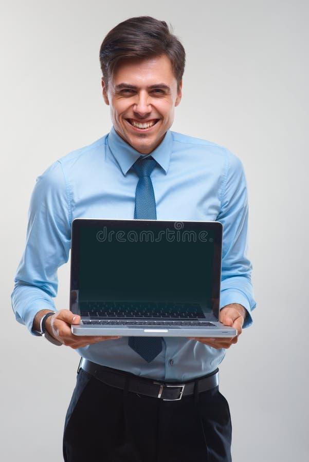 Biznesowy mężczyzna trzyma laptop przeciw białemu tłu obraz stock
