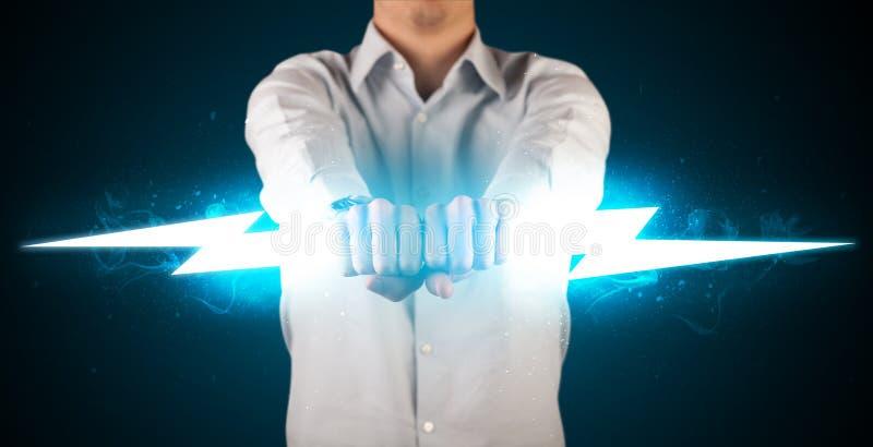 Biznesowy mężczyzna trzyma rozjarzonego błyskawicowego rygiel w jego ręki zdjęcia stock