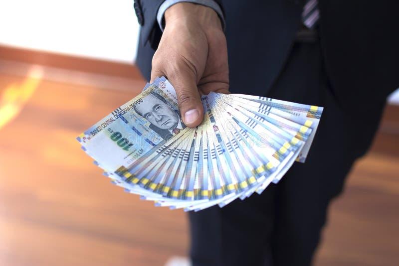 Biznesowy mężczyzna trzyma 100 zeluje rachunki w fan, peruvian waluty pojęcie zdjęcia stock