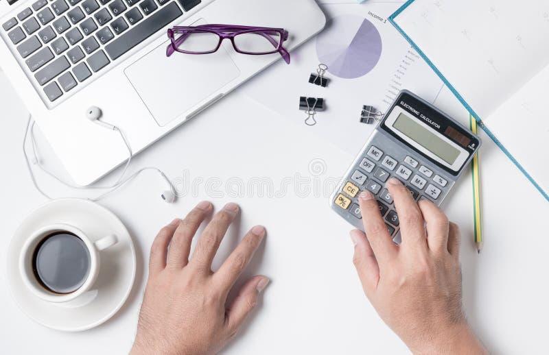 Biznesowy mężczyzna używa kalkulatora na nowożytnym białym biurowego biurka stole zdjęcia stock