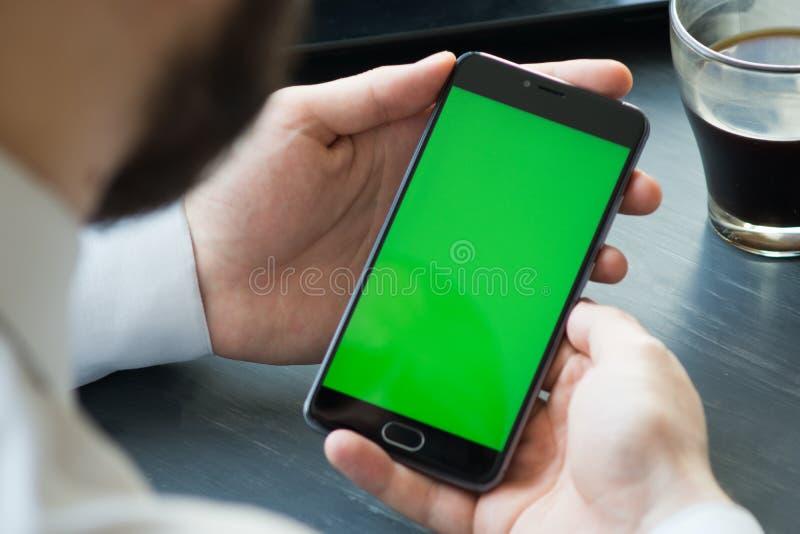 Biznesowy mężczyzna używa mądrze telefon z zieleń ekranem dla interneta fotografia stock