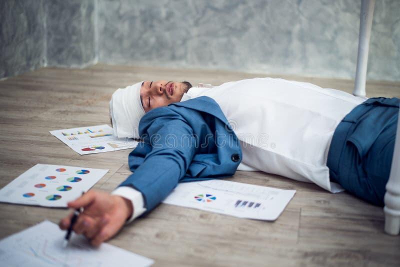 Biznesowy mężczyzna w kostiumów kłamać nieświadomie na podłodze w biurze zdjęcie stock