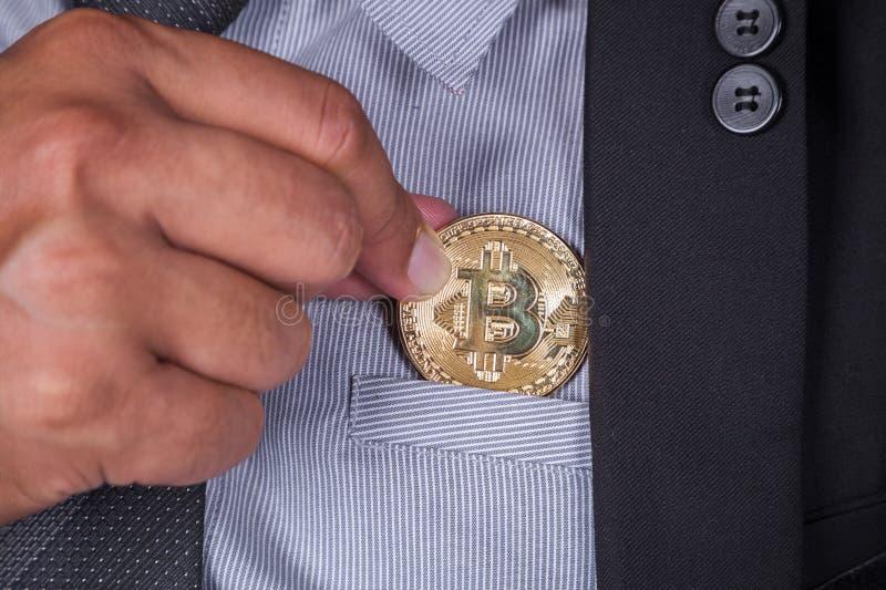 Biznesowy mężczyzna w kostiumu wyboru bitcoin wewnątrz wkładać do kieszeni zdjęcie stock