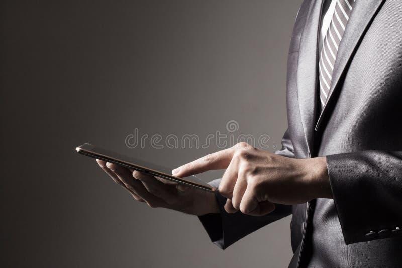 Biznesowy mężczyzna w Popielatej kostiumu mienia pastylki technologii wzruszającym ogólnospołecznym medialnym pojęciu zdjęcie stock