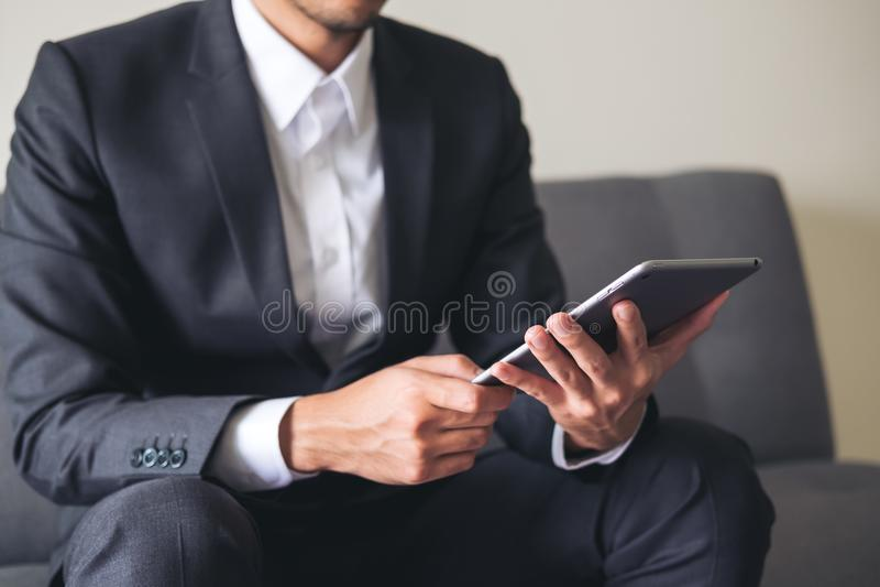 Biznesowy mężczyzna w szarym kostiumu obsiadaniu na kanapy mieniu, używać pastylka komputer osobistego i patrzejący dla pracy obrazy royalty free