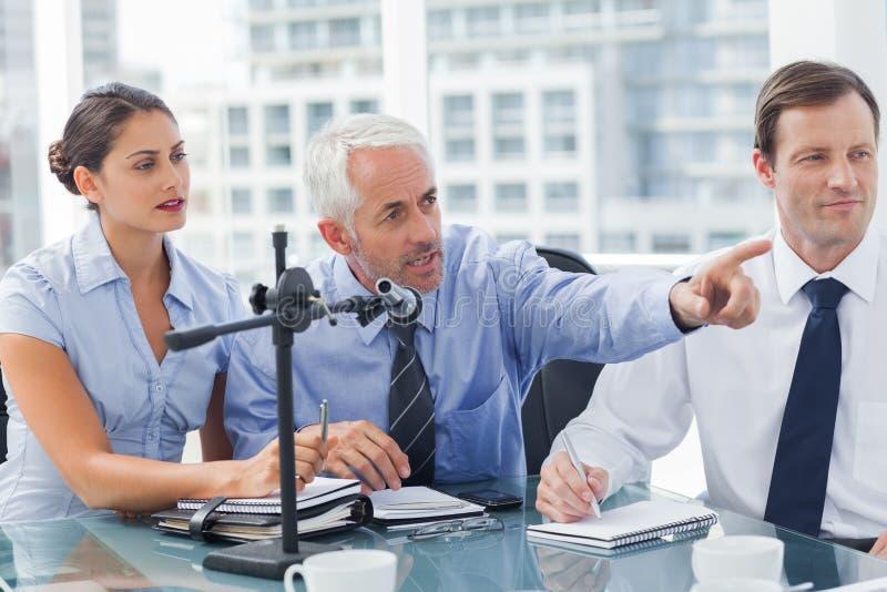 Biznesowy mężczyzna wskazuje przy coś w konferenci zdjęcia stock