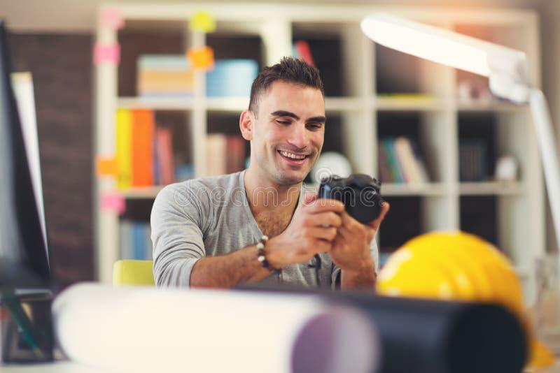 Biznesowy mężczyzna z cyfrową kamerą przy biurowym biurkiem zdjęcie stock