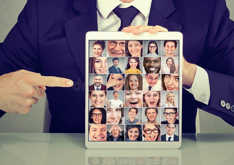 Biznesowy mężczyzna z pastylki fotografii kolekci reklamową grupą wielokulturowi różnorodni ludzie obrazy stock