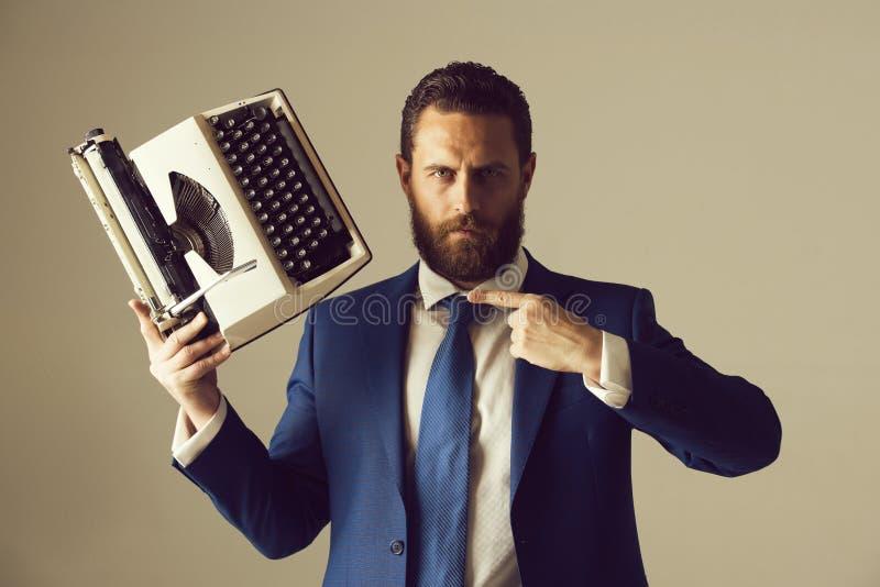 biznesowy m??czyzna w b??kitnym krawacie z maszyna do pisania i kostiumu obrazy stock