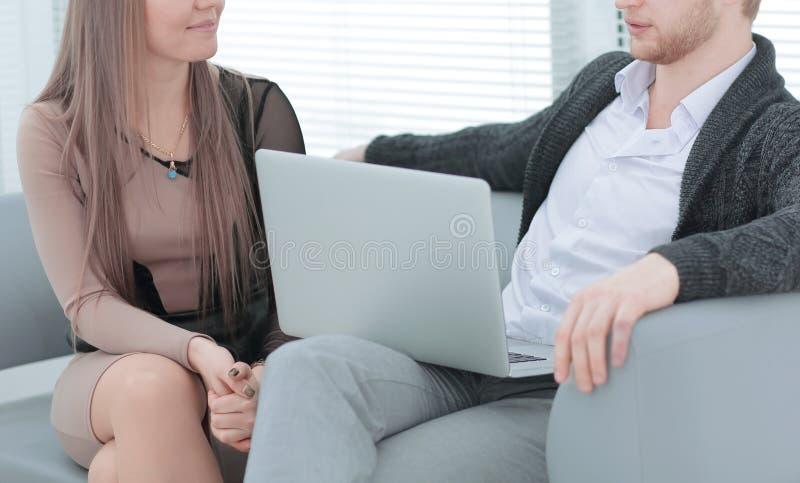 Biznesowy pary obsiadanie w działaniu i biurze - opowiadający obraz stock