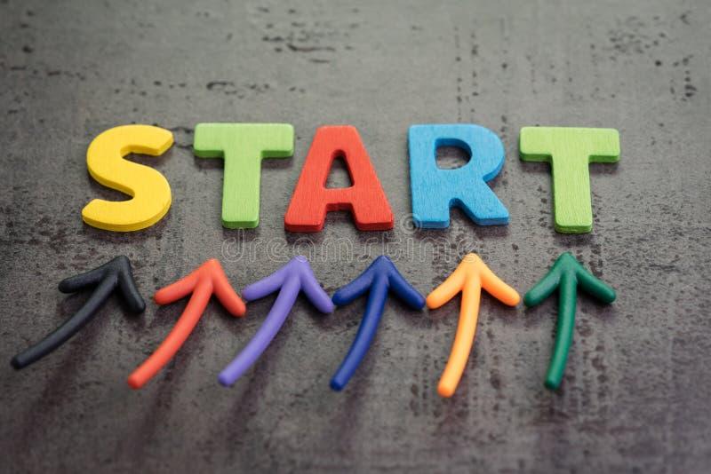 Biznesowy początek lub zaczyna nowego życie podróży pojęcie, kolorowy strzała punkt do słowa początek na blackboard cementu ścian zdjęcie stock