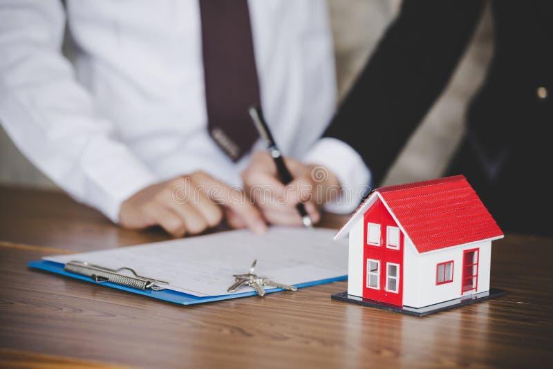 Biznesowy podpisywanie kontrakt i dom z kluczami na stole, obraz stock