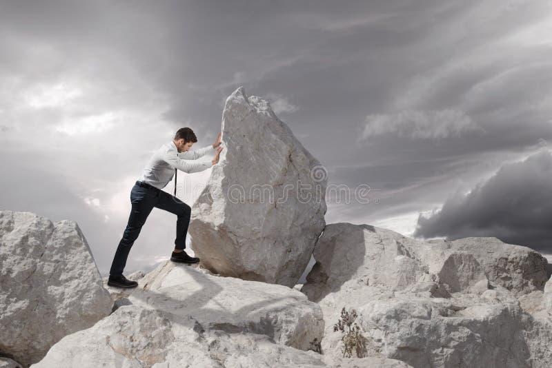 Biznesowy pojęcie, Młody biznesmena dosunięcia ampuły kamień ciężki z kopii przestrzenią zdjęcia royalty free