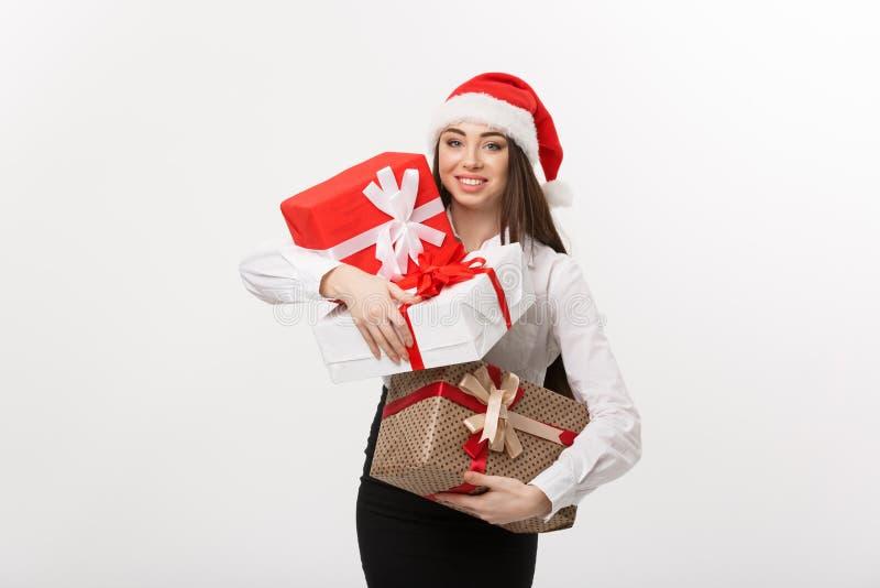 Biznesowy pojęcie - Piękna młoda caucasian biznesowa kobieta trzyma mnóstwo boże narodzenie prezenta pudełka z z Santa kapeluszem obrazy stock