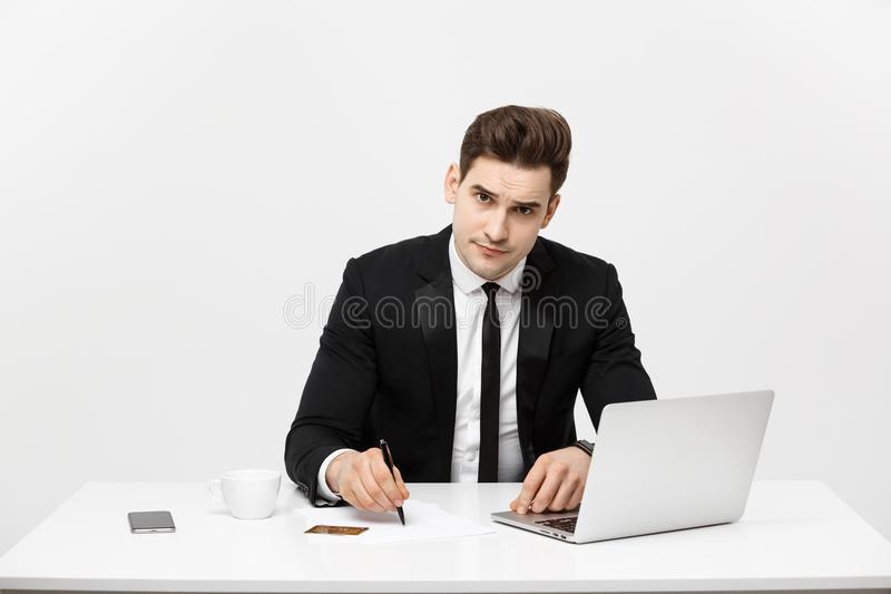 Biznesowy pojęcie: Portret koncentrował młodych pomyślnych biznesmena writing dokumenty przy jaskrawym biurowym biurkiem fotografia stock