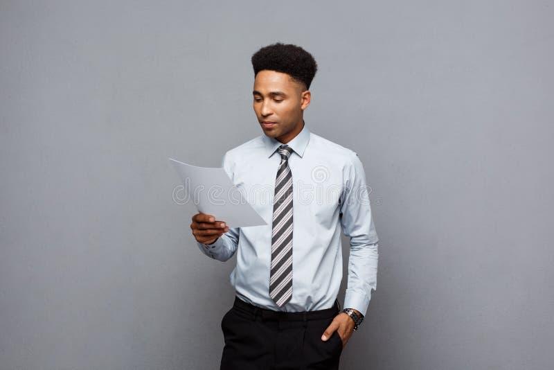 Biznesowy pojęcie - przystojny młody fachowy amerykanina afrykańskiego pochodzenia biznesmen koncentrował czytanie na dokumentu p zdjęcie royalty free
