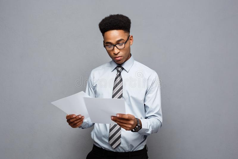 Biznesowy pojęcie - przystojny młody fachowy amerykanina afrykańskiego pochodzenia biznesmen koncentrował czytanie na dokumentu p zdjęcia stock