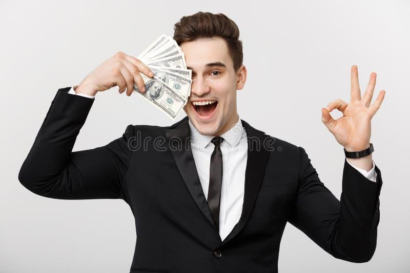 Biznesowy pojęcie: Ufny młody biznesmena mienia pieniądze i seansu ok podpisujemy bielu popielatego tło obrazy stock