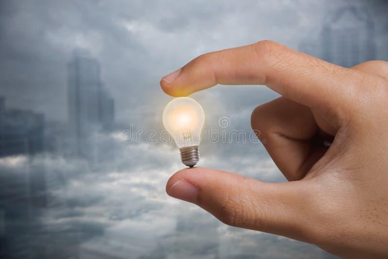Biznesowy ręki mienie iluminował żarówki pojęcie dla pomysłu zdjęcie royalty free