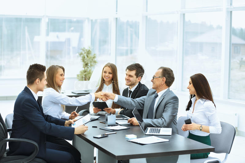Biznesowy spotkanie przy uściskiem dłoni partnery biznesowi i stołem fotografia royalty free