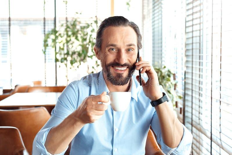 Biznesowy styl życia Handlowa obsiadanie przy kawiarnią pije gorącą kawę opowiada na smartphone przyglądającej kamerze szczęśliwe obrazy royalty free