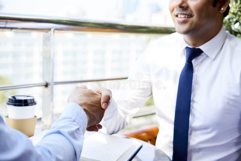 Biznesowy uścisk dłoni w kawiarni obraz royalty free