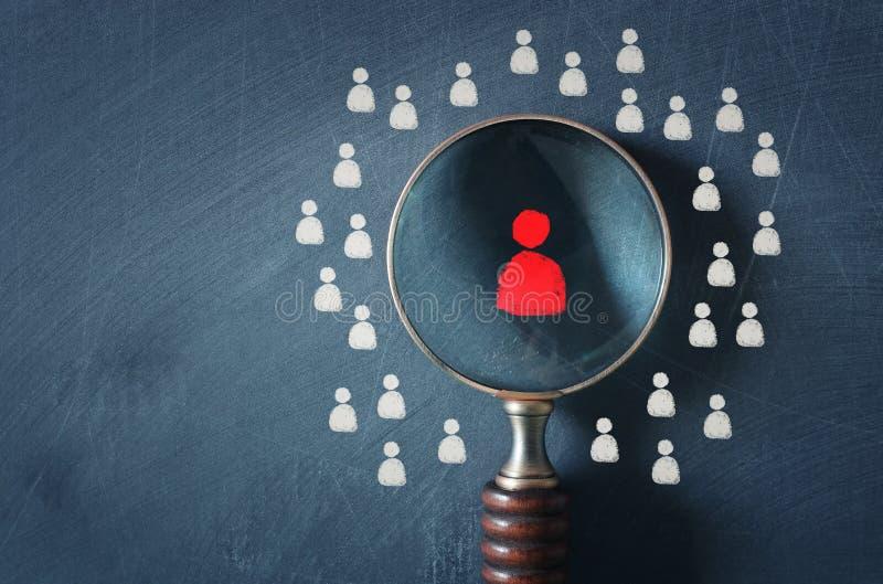 Biznesowy wizerunek buduje silnej drużyny powiększać - szkło z ludźmi ikony nad chalkboard tłem, dział zasobów ludzkich i zdjęcie stock