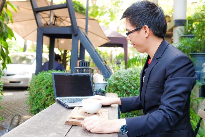 Biznesowy wygodny azjatykci mężczyzna pracuje na laptopie z filiżanką obraz royalty free