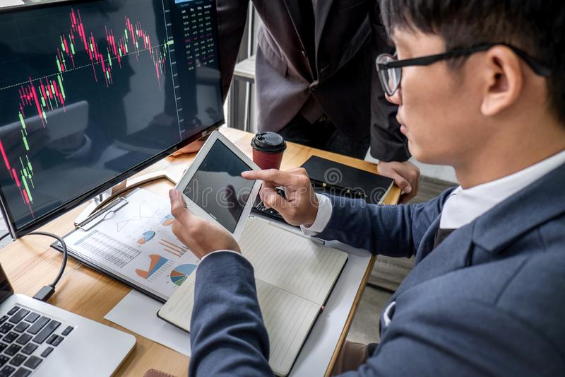 Biznesu drużynowy inwestorski działanie z komputerem, planowaniem i analizować wykresu rynek papierów wartościowych handel z akcy obrazy royalty free