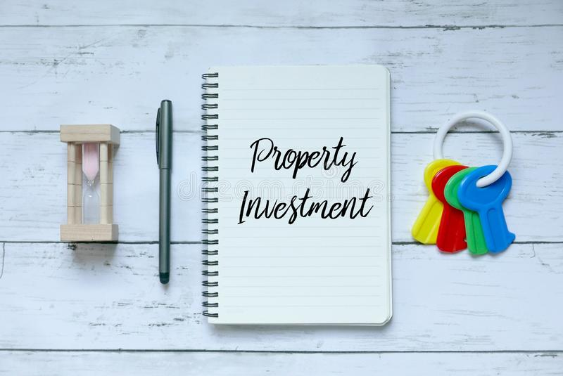 Biznesu, finanse i własności pojęcie, Odgórny widok piaska zegar, pióro, klucze i notatnik pisać z Majątkową inwestycją, obraz stock