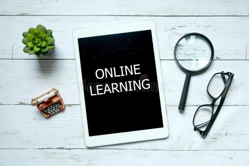 Biznesu i edukacji pojęcie, Odgórny widok roślina, powiększa - szkło, szkła i pastylka komputer osobisty pisać z Online uczenie, obrazy stock